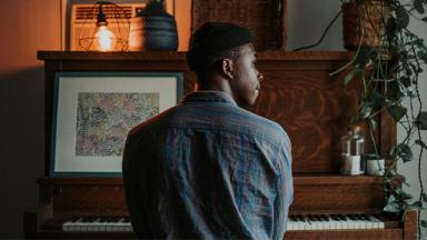 person with their back to the camera, sitting at a piano, looking out the window