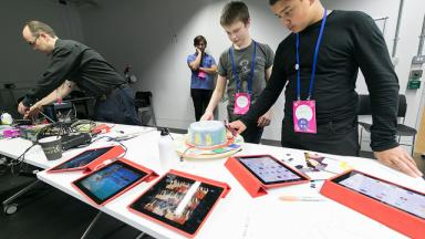 young people wearing lanyards looking down at different Ipads laid out on the table