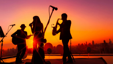 Three musicians silhoutted against a sunset