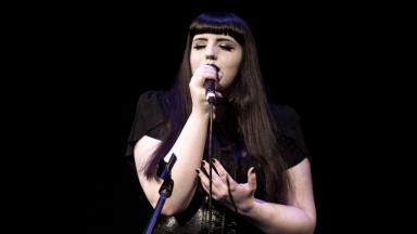 Young person with dark hair, wearing all black clothing, singing into a mic
