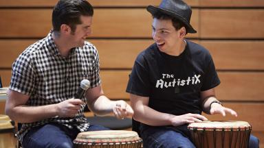 Two people playing standing drums, one wearing a t-shirt reading The Autistix