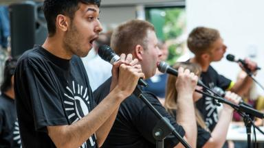 Four musicians singing into microphones
