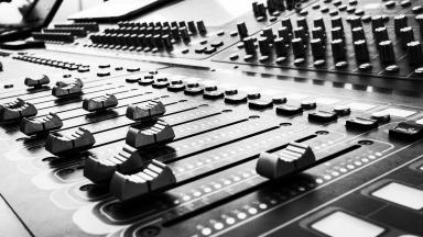 Black and white photo of music mixer board.