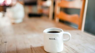 "A coffee table with a mug of black coffee, with ""Begin"" written on the mug."