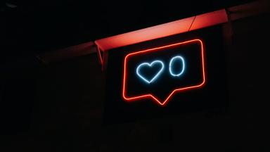 Neon light in the shape of a notification bubble, a heart shape to represent the number of likes, and the number 0 next to it.