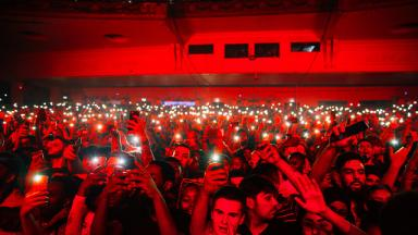 a crowd in a music venue all pointing their phones towards the camera, bathed in red light