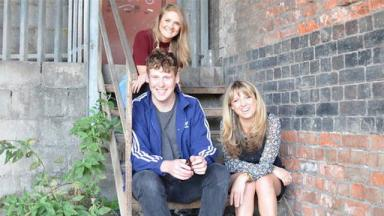 three people sitting on stairs outside of a building, a plant growing on the left