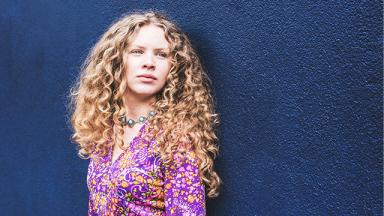 woman with long blonde curly hair in pink shirt against navy blue background