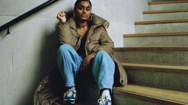 Photo of young musician, Pritt sitting on the stairs, wearing a puffy coat and baggy jeans