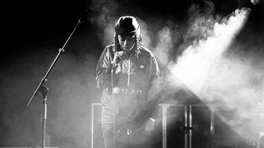 black and white photo of a young person singing on stage with smoke and lights around them