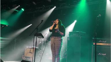 woman singing into microphone on a stage, under green lights