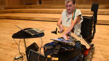Musician playing adaptive instruments including guitar, keyboard and laptop