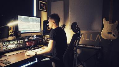 Person in music studio, using music software on their computer.