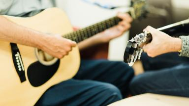 two people playing guitars, only the guitars and their hands are visible