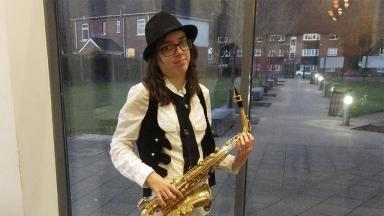 person wearing white shirt and black waistcoat holding a saxaphone. Standing in front of a glass door, houses on a street visible