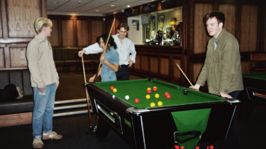 Press shot of band English Teacher, with the four band members in a pub playing Snooker.