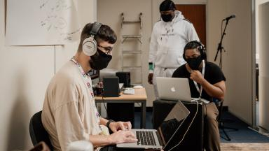 three people in a room wearing face masks working on laptops