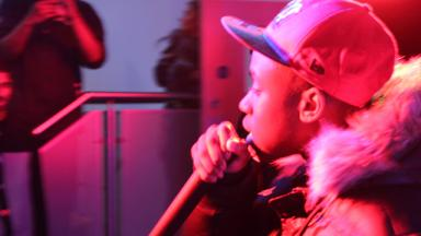 young person wearing a coat and cap rapping into the microphone, bathed in a red light