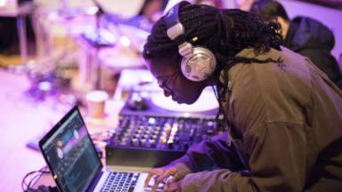 girl with headphones in producing music on a laptop