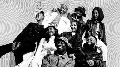 black and white photo of a group of people sitting together smiling