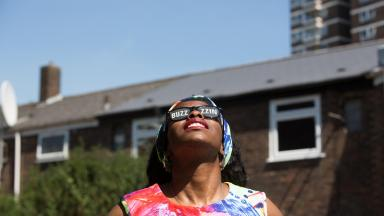 woman looking up at the sky wearing sunglasses that say buzzing