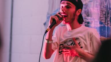 Lil Trubz rapping into a microphone in a white t-shirt