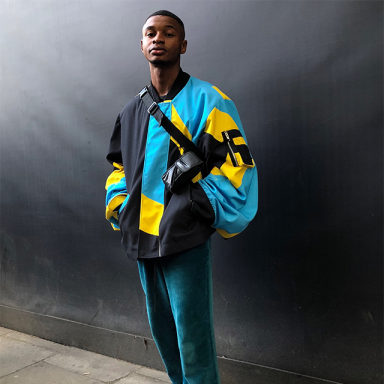 young person wearing a blue jacket against a black background