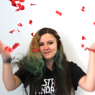 person with blue dip-dyed hair throwing rose petals in the air