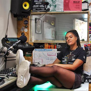 Young person with long braids, wearing all black with white trainers and sitting in a studio with her feet resting on the table.