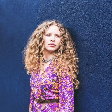 Young woman with long curly hair and wearing a purple patterned dress.