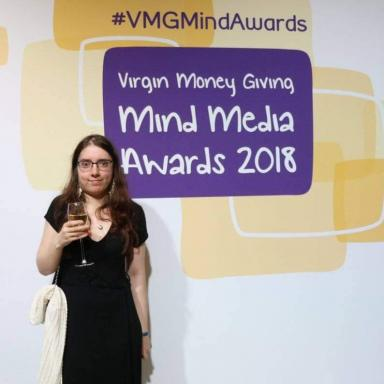"Young person with brown hair, wearing a black dress, standing in front of a poster that says ""Mind Media Awards 2018""."