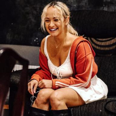 Candid photo of young person laughing, with blonde hair and wearing a white dress, orange jacket and black boots.