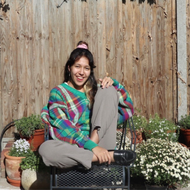 Photo of Alice Reid in her garden, sitting in a chair with her knee up, and smiling.
