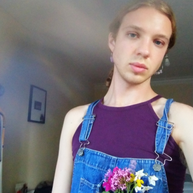 Selfie image of Harry Lindsey, wearing a purple top and denim dungarees with a small bouquet of flowers in the front pocket.