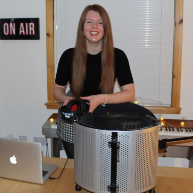 Image of Kara Conway, in a radio studio and smiling to the camera